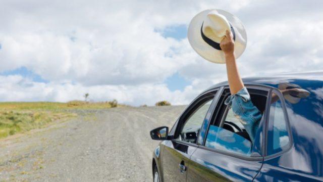 マシンウィンドウで帽子を保持している女性の手
