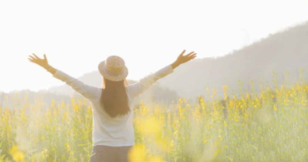 草原の中で手を広げる女性